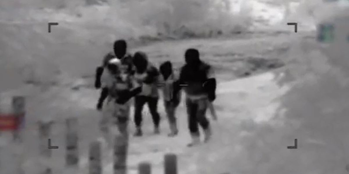 Caught on video: Woman, son cross fence after being dropped off by heavily armed escort