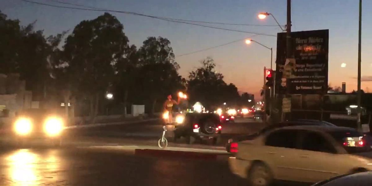 Unicycling man balances while juggling flaming pins in middle of busy intersection